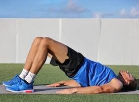 Trainer exercises glute bridge