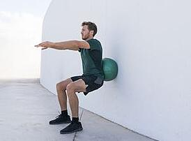 trainer exercises ball squat